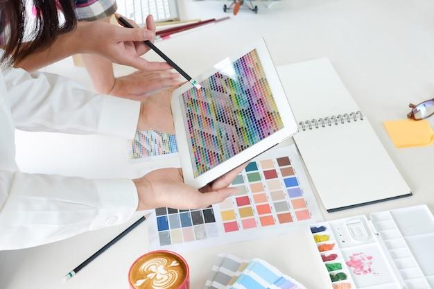 Sluit de vergadering van de kunstenaarsbespreking met kleuren planningsproject in tabletcomputer.