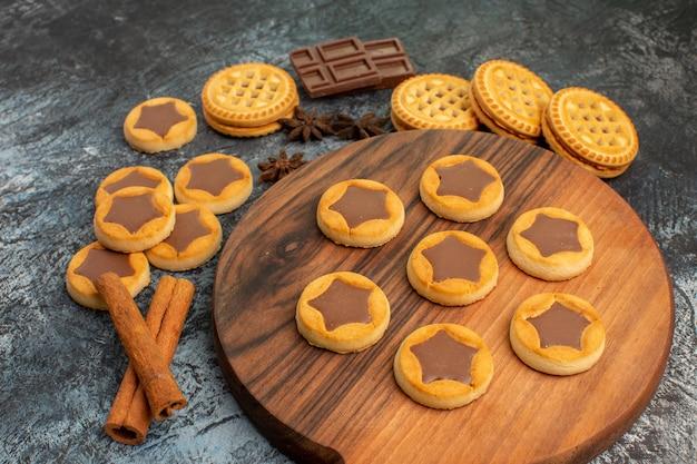 Sluit de zijwaartse opname van koekjes op een houten schaal en kaneel en chocolaatjes op grijs