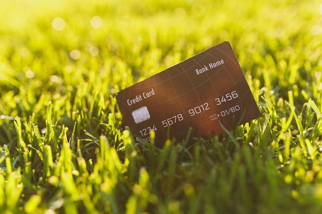Sluit de zwarte creditcard van de creditcard op levendig lentegroen vers golfgras, zonneschijngazon. natuur textuur, groene achtergrond voor behang. zachte focus. veld of financiën conceptontwerp. ruimte kopiëren.