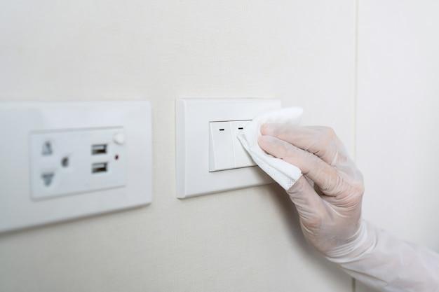 Sluit een hand in handschoen met een vochtig doekje om een oppervlak te desinfecteren