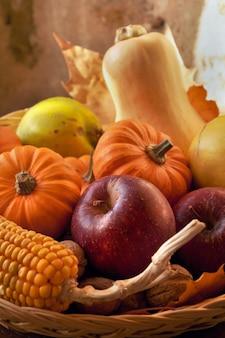Sluit een mand vol pompoenen, appels en maïs binnenshuis