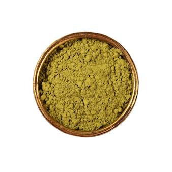 Sluit een metalen kom vol met gemalen ongebrande rauwe groene arabica-koffie geïsoleerd op wit, verhoogde bovenaanzicht, direct erboven
