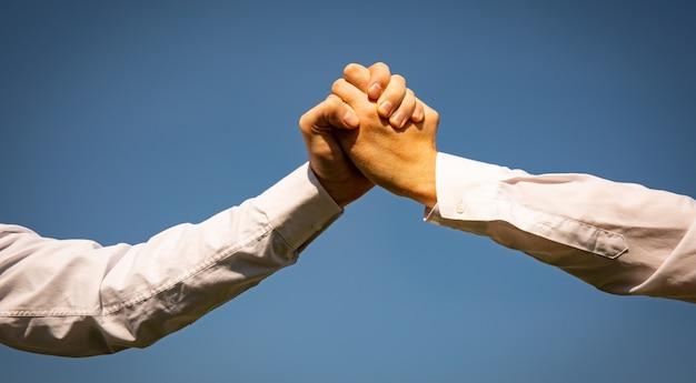 Sluit een paar helpende biddende handen op de mooie hemelachtergrond van de zonsopgangwazig om te sparen voor steunmensen en sociaal afstandsconcept.
