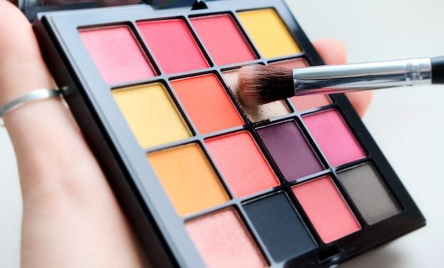 Sluit een palet met kleurrijke oogschaduw en een make-upborstel. decoratieve damescosmetica. visagiste. avond- en ochtendmake-up.