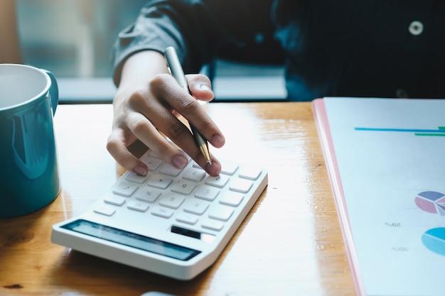 Sluit een rekening die over financieel met calculator op kantoor werkt om uitgaven, boekhoudkundig concept te berekenen.