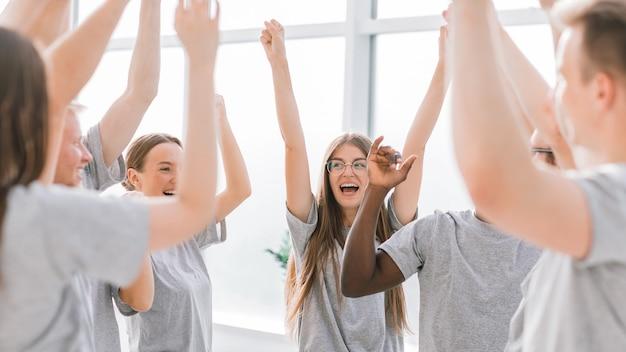 Sluit een team van gelukkige jonge mensen die hun eenheid tonen their Premium Foto
