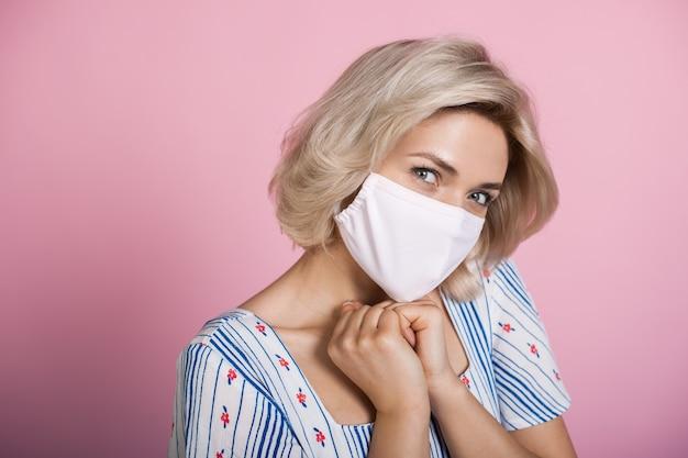 Sluit foto van een blanke blonde vrouw met een medisch masker camera kijken en geluk gebaren