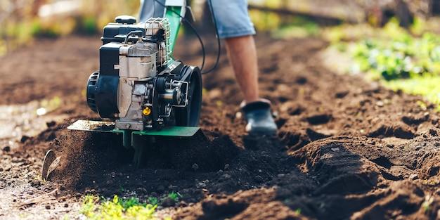 Sluit foto van jonge landbouwerstuinman cultiveren rototiller van de grondgrond