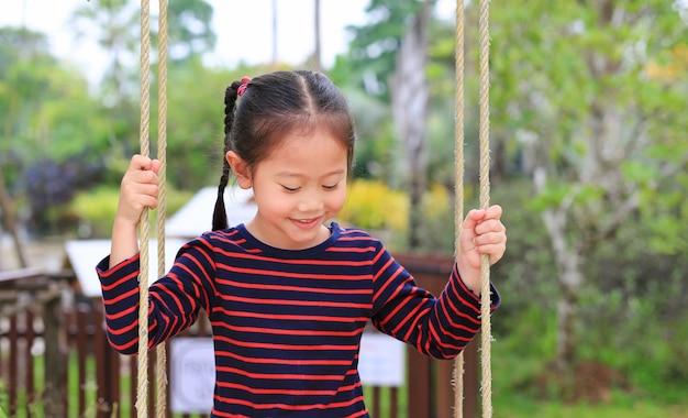 Sluit gelukkig weinig het aziatische spel van het kindmeisje en zit op de schommeling in het aardpark.