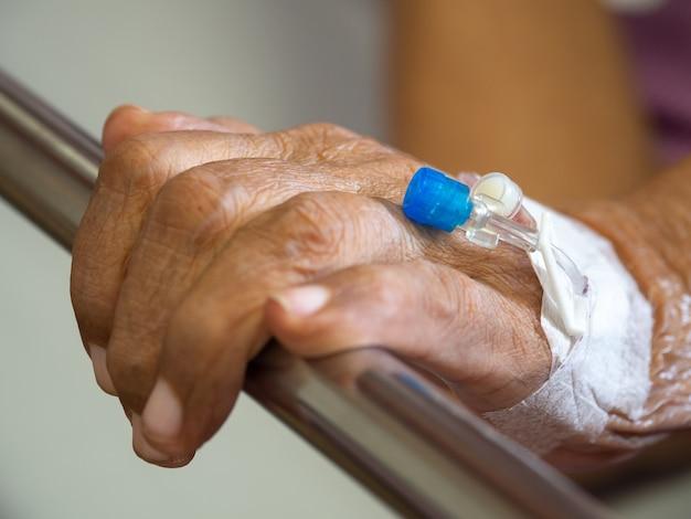 Sluit hand van de hand de geduldige bejaarde met zoute intraveneuze (iv) oplossing in het ziekenhuis.
