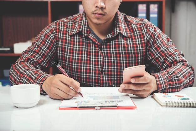 Sluit jonge mens omhoog het werken en slimme telefoon en laptop