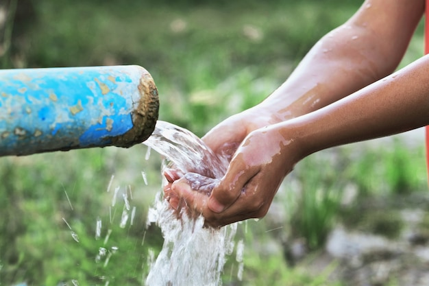 Sluit kinderen omhoog hand en waterdaling plons in pijp
