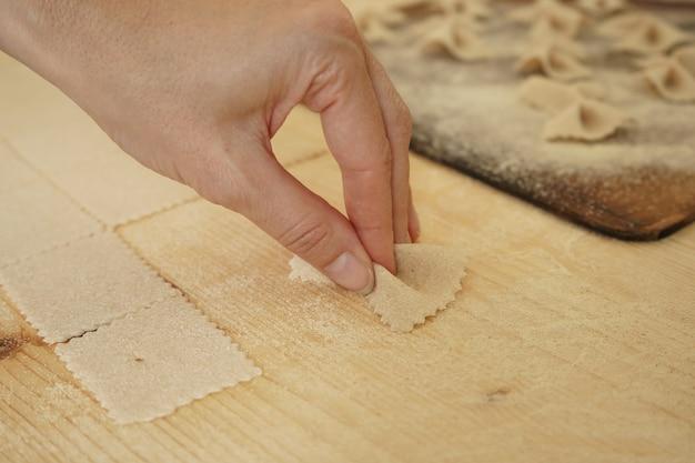 Sluit macrodetail van proces van eigengemaakte veganistische farfalle deegwaren. de kok vormt het deeg