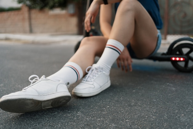 Sluit meisjesbenen omhoog zittend op haar elektroautoped in de zomer op straat