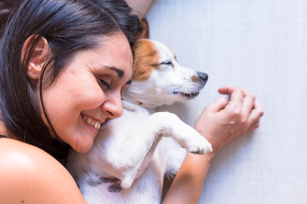 Sluit mening die van hond op de vloer met zijn eigenaar omhoog ligt. vrouw met haar ogen dicht. lifestyle binnenshuis en liefde voor dieren concept