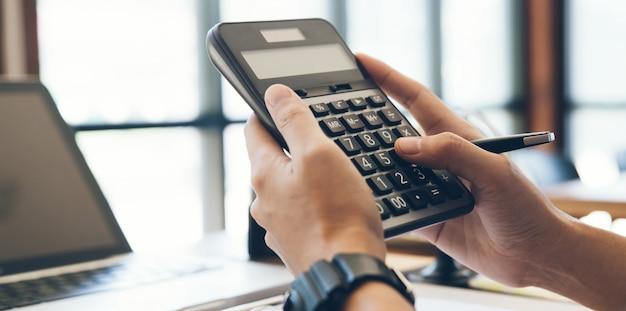 Sluit mensenhanden omhoog gebruikend calculator bereken over kosten thuis office.tax, boekhouding, statistieken en analytisch onderzoekconcept