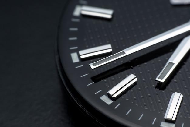 Sluit met de wijzers van de klok mee op zwarte wijzerplaatachtergrond. polshorloge in retro-stijl