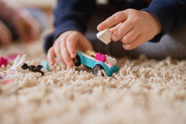 Sluit nadrukmening van plastic stuk speelgoed auto van blokken omhoog terwijl weinig jongen het maken van een nieuwe vorm overhandigt.
