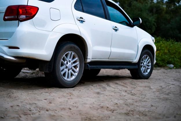 Sluit omhoog 4x4 van wegauto die zich op de zandige oppervlakte in strand met aanhangwagen d bevinden