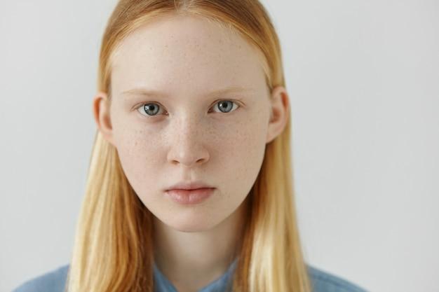 Sluit omhoog aantrekkelijk jong europees wijfje met lang blond haar, sproeten en mooie blauwe ogen die geen make-up dragen die serieuze blik hebben