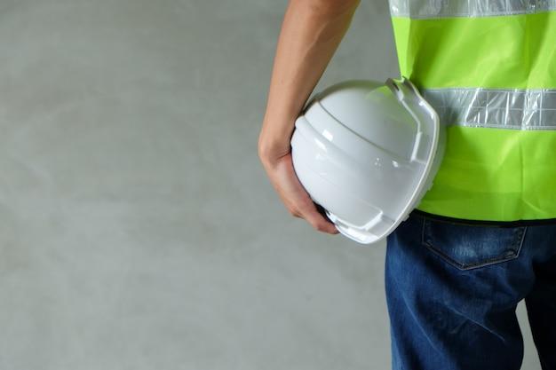 Sluit omhoog achtermening van bouwer, ingenieur, arbeider draag het veiligheidsvest
