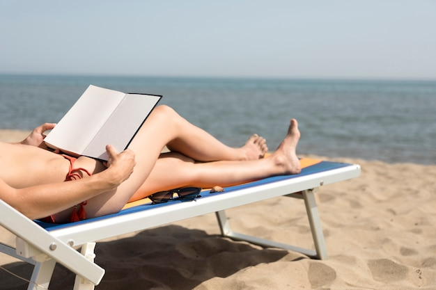 Sluit omhoog achtermeningsvrouw op strandstoellezing