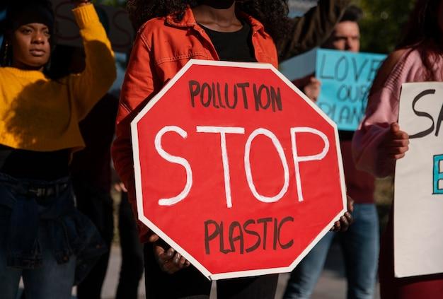 Sluit omhoog activisten die met stopbord protesteren