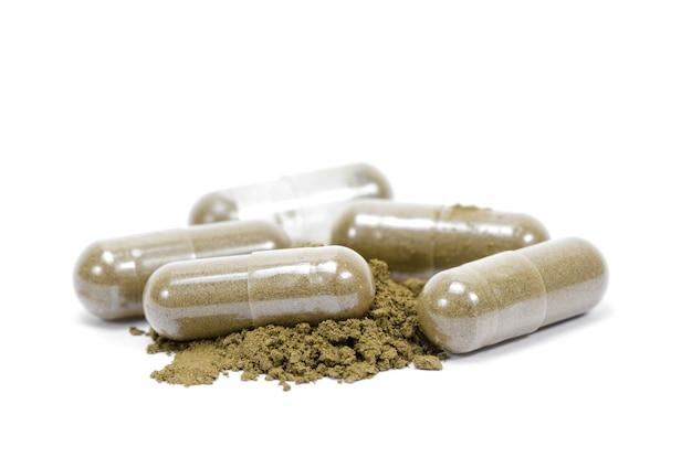 Sluit omhoog andrographis paniculata kruiden antipyretic capsules die op wit worden geïsoleerd