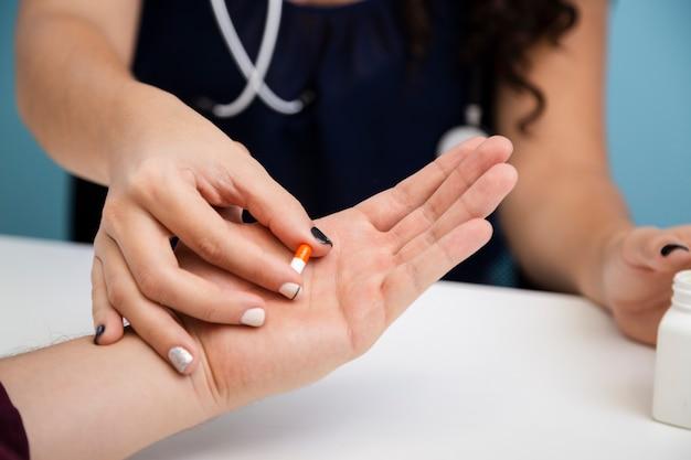 Sluit omhoog arts die een pil geeft