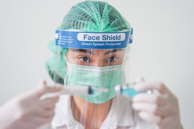 Sluit omhoog arts die gezichtsschild, medisch masker en medisch bosje dragen. ze hield een injectiespuit en fles vast met het coronavirus-vaccin voor het 2019-ncov covid-virus.