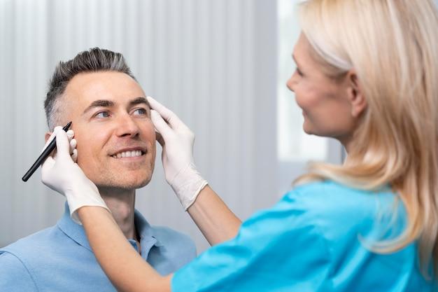 Sluit omhoog arts die smileypatiënt controleert