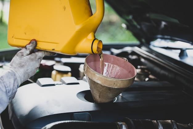Sluit omhoog autowerktuigkundige hand die en verse olie gieten vervangen in motor van een auto bij autoreparatiegarage. automobiel onderhoud en industrie concept