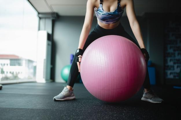 Sluit omhoog aziatisch vrouwenmodel houdt yogabal bij gymnastiek voorbereidingen treffend voor oefening, oefeningsmeisje