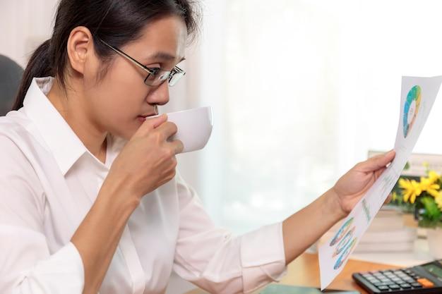 Sluit omhoog aziatische bedrijfsvrouwen die de grafiek van het analyserapport thuis werken. mensen uit het bedrijfsleven kijken werkplan papier bij de hand.