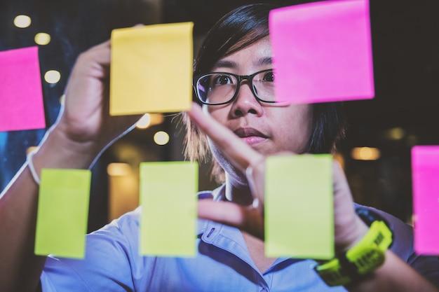 Sluit omhoog aziatische onderneemster die een plan op kleverige nota's schrijven