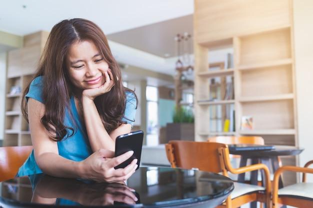 Sluit omhoog aziatische vrouwen die blauwe overhemden dragen zit tekst het typen in een mobiele telefoon