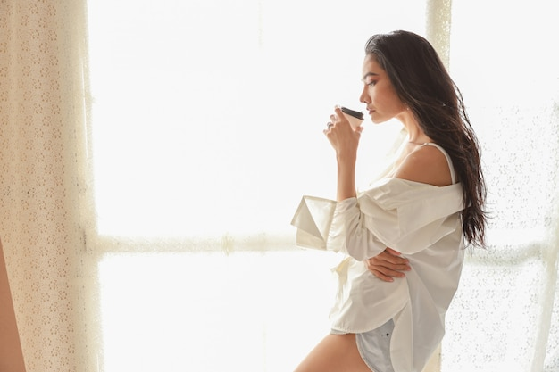 Sluit omhoog aziatische vrouwenkunstenaar in het witte overhemd drinken koffie en ontspan terwijl het trekken van beeld met potlood (het concept van de vrouwenlevensstijl)