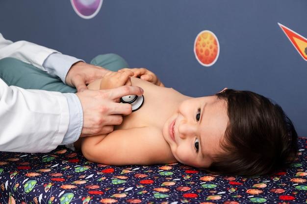 Sluit omhoog baby die met stethoscoop wordt onderzocht