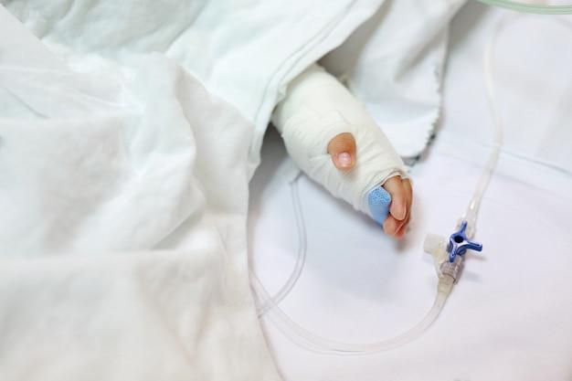 Sluit omhoog babyhand op het bed van de patiënt in het ziekenhuis met intraveneus zout.