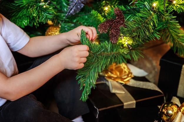 Sluit omhoog babyhanden thuis het verfraaien van kerstboom
