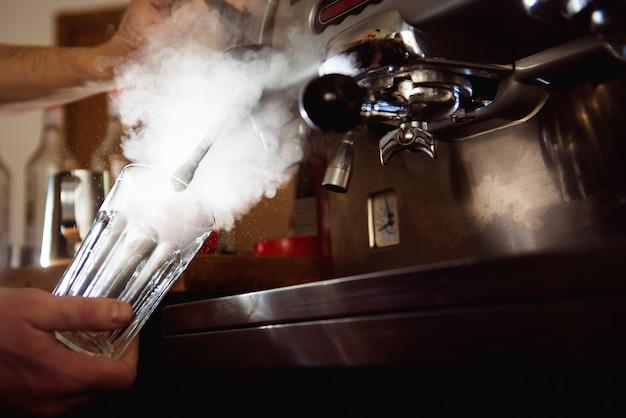 Sluit omhoog baristahanden makend koffiekop met koffiemachine in koffiewinkel