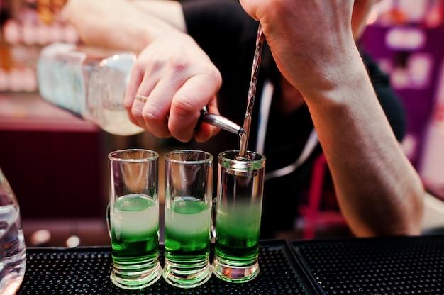 Sluit omhoog barmanhanden voorbereidend groene mexicaanse cocktaildrank bij de bar