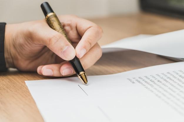 Sluit omhoog bedrijfsvrouw die termijnen van overeenkomstdocument ondertekenen op houten lijst