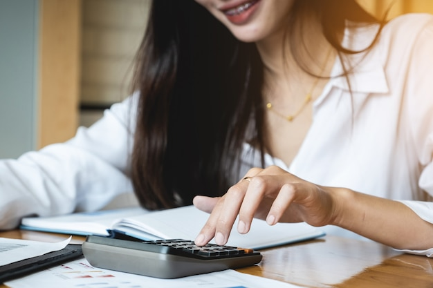 Sluit omhoog bedrijfsvrouw gebruikend calculator en laptop voor wiskundefinanciering