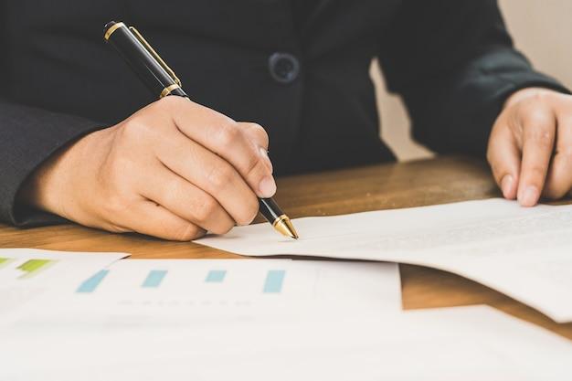 Sluit omhoog bedrijfsvrouw ondertekeningsvoorwaarden van overeenkomstendocumenten op haar bureau