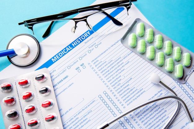 Sluit omhoog beeld van een medische geschiedenisvorm, medische tabletten of pillen en een artsenstethoscoop met glazen.