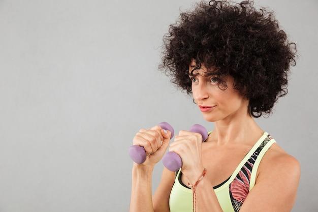Sluit omhoog beeld van geconcentreerde krullende geschiktheidsvrouw die oefening doet
