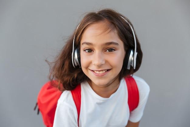 Sluit omhoog beeld van gelukkige donkerbruine schoolmeisje het luisteren muziek