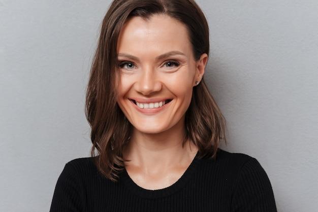 Sluit omhoog beeld van glimlachende vrouw die in zwarte kleding de camera op grijs bekijken