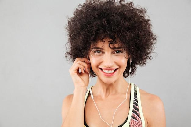 Sluit omhoog beeld van het glimlachen van krullende geschiktheidsvrouw het luisteren muziek